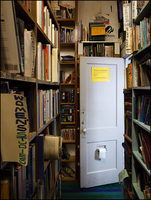 A Facebook sign hangs on the inside of the restroom door, above the toilet paper roll, at Hyde Brothers Books in Fort Wayne, Indiana. Seen looking down an aisle of old books.