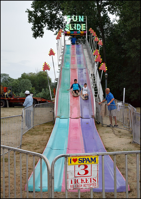 An I Love SPAM bumper sticker on the sign in front of the Fun Slide at the Three Rivers Festival in Fort Wayne, Indiana. Two children slide down the giant three-lane slide.