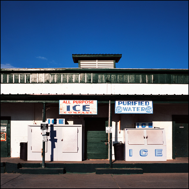 Two large freezers sit on the loading dock at the All Purpose Ice Company in Artesia, New Mexico. A sign on the awning advertises purified water for 25 cents.