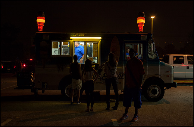 People line up in the dark to buy ice cream cones from a food truck after the Fourth of July fireworks in Fort Wayne, Indiana.