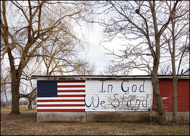An American flag with no stars painted on a barn next to a sign that says In God We Stand. The barn is on South County Line Road in rural Allen County, Indiana.