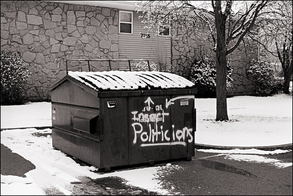 Graffiti that says Insert Politicians is spray-painted on a dumpster at Hickory Creek Apartments in Waynedale as a political protest.