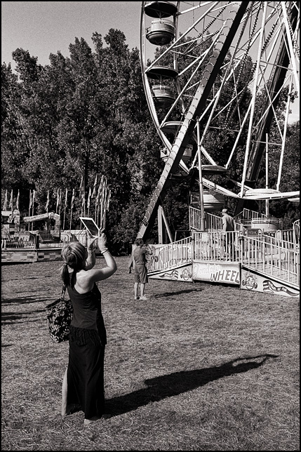 A woman photographing a ferris wheel with the camera in her Apple iPad at the 2015 Three Rivers Festival in Fort Wayne, Indiana.