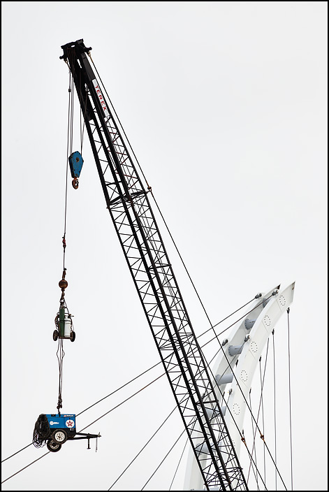 A portable generator and a set of welding tanks hang from a crane above a bridge construction site to prevent theft after the workday has ended. Cable-stayed bridge over Coliseum Boulevard, connecting IPFW and Ivy Tech in Fort Wayne, Indiana.