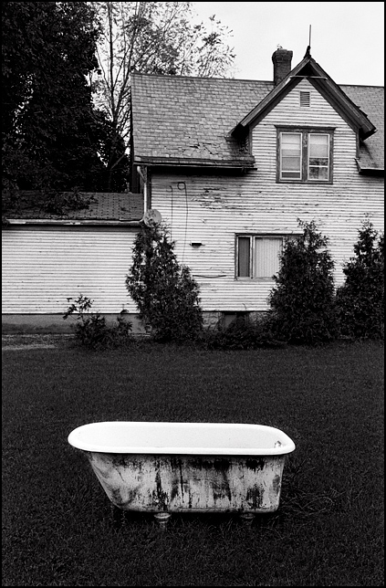 An old cast iron bathtub sits next to a house that is being renovated on Spy Run Avenue in downtown Fort Wayne, Indiana.
