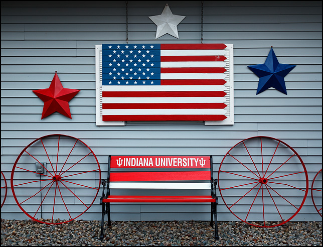 A park bench with the Indiana University logo sits under a wooden American flag in front of a house on Bluffton Road in rural Allen County, Indiana. Red white and blue metal stars and old steel wagon wheels flank the bench and flag.