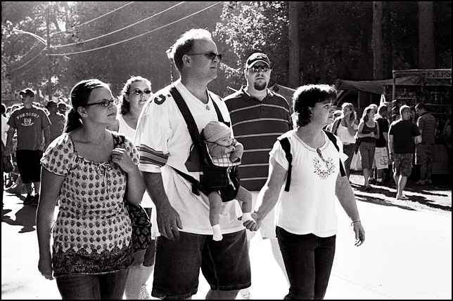 A man carries his baby grandson in a harness on his chest while the baby's mother walks beside them holding the baby's foot as the family walks through the Johnny Appleseed Festival in Fort Wayne, Indiana.