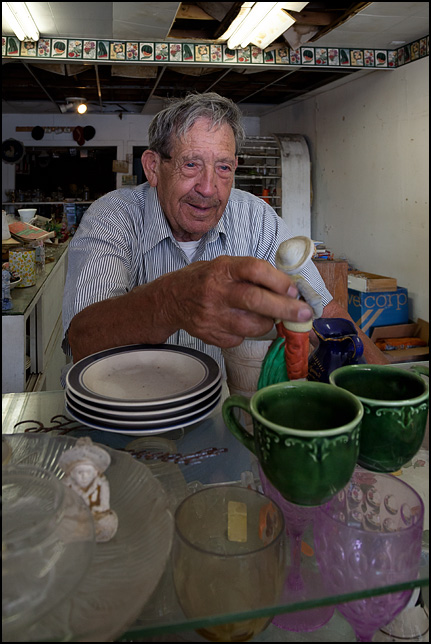 Elderly antique dealer Jack Francis examines a ceramic figurine on a shelf full of old glassware at Jacks Antiques in Wabash, Indiana.