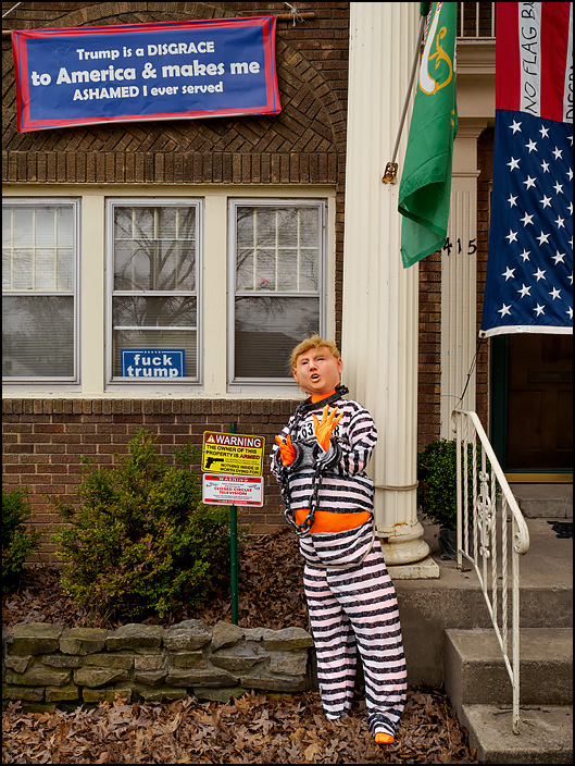 An effigy of President Donald Trump wearing a striped prison uniform and shackles stands in front of a house on Oakdale Drive in Fort Wayne, Indiana. Signs in the windows say Fuck Trump, and a banner declares that Trump is a disgrace to America.