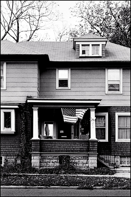 A large American flag and a smaller one together on the porch of an old house on Jefferson Boulevard in the West Central Neighborhood in downtown Fort Wayne, Indiana.
