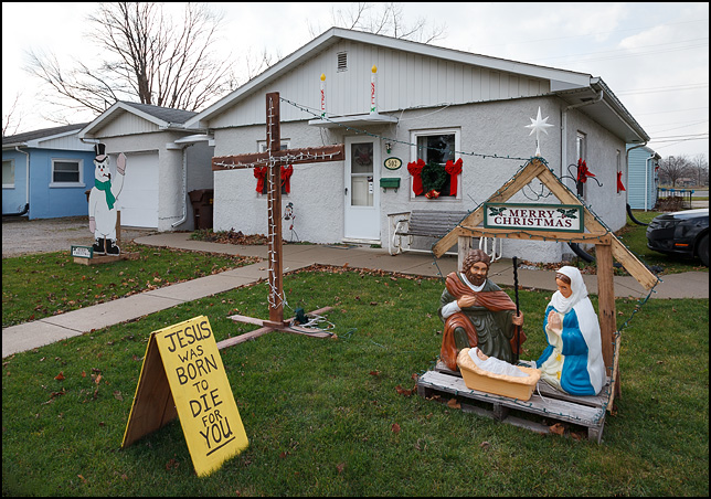 Christmas decorations in front of a house in the small town of Churubusco, Indiana. There is a nativity scene and a sign that says, Jesus was born to die for you.