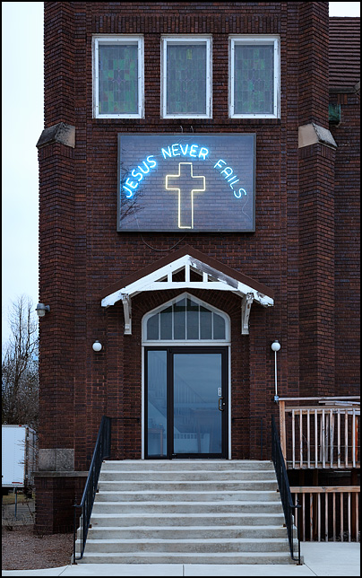 A neon sign with a cross that says Jesus Never Fails. It hangs above the entrance to Sparta United Church of Christ on US-33 in the small town of Kimmell, Indiana. Photographed at first light in the morning before sunrise.