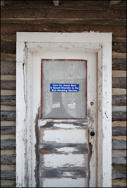 The door on abandoned log cabin with a bumper sticker on the window that says, Live For Jesus Now and Spend Eternity in the Non-Smoking Section.