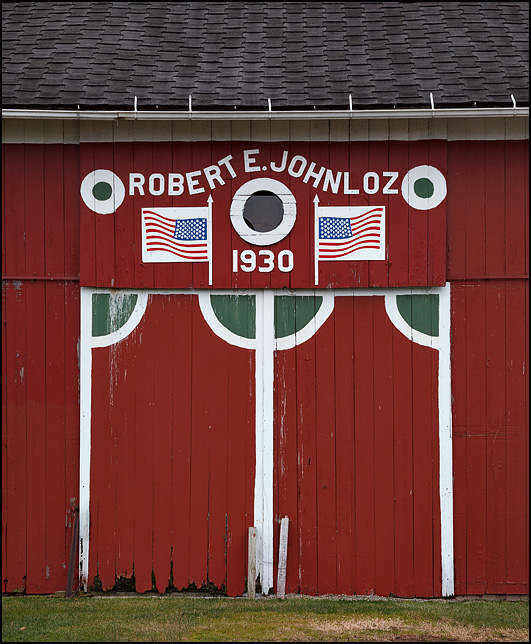 American flags and a sign that says Robert Johnloz 1930 hang over the main doors of an old red barn on US-224 in Wells County, Indiana.