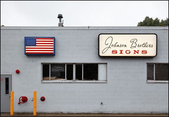 A backlit American flag sign hangs on the front of the gray cinderblock Johnson Brothers Signs building on State Road 5 in South Whitley, Indiana.