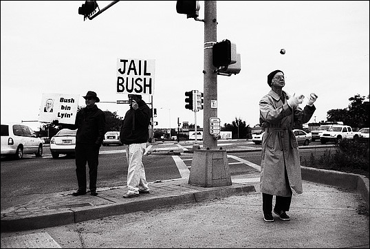 A peace activist juggling tennis balls to attract attention to the anti-war protest. They are protesting president bush and the war in Iraq with signs that read Jail Bush and Bush Bin Lyin.