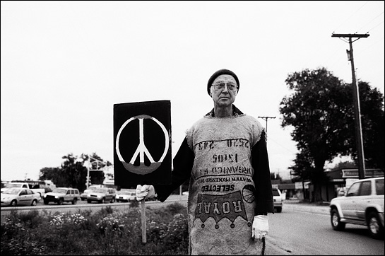 A peace activist wearing an old burlap sack holds a peace sign during a protest against the Iraq War.