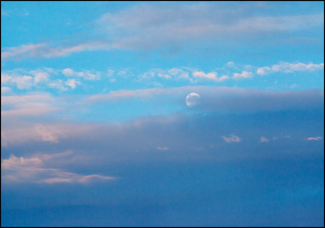 The moon peeks out from behind a line of clouds in the early morning sky at dawn over Fort Wayne, Indiana.
