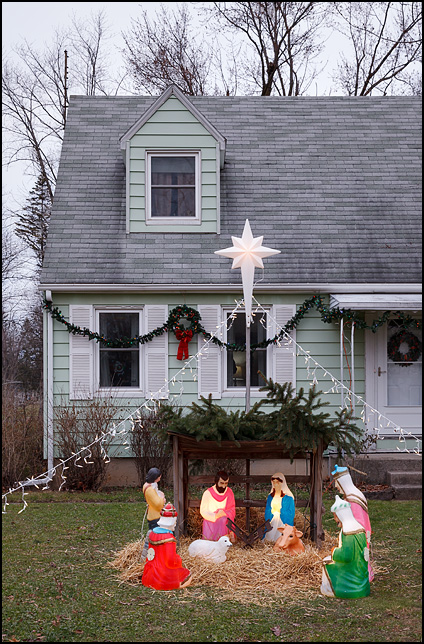 A nativity scene with glowing plastic figures of Jesus, Mary, Joseph, and the three wise men with a large plastic star and Christmas lights in front of a house in Fort Wayne, Indiana.