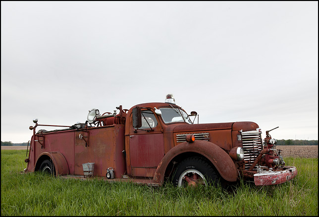 An abandoned late 1940s International KB-7 fire truck sits on the edge of a field in rural Adams County, Indiana.