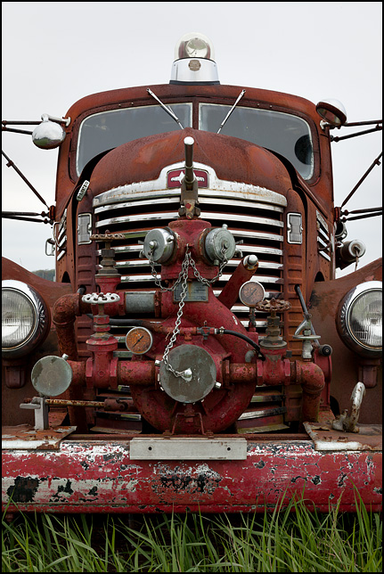 The front of an abandoned late 1940s International KB-7 fire truck, showing the grille and the pumping equipment mounted on the it.