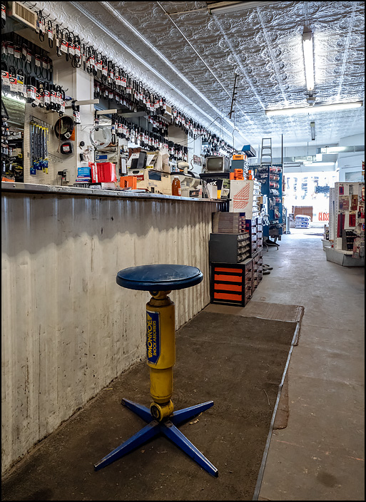 A stool that looks like a Monroe Shock Absorber stands in front of the sales counter at Kendallville Auto Parts on Main Street in the small town of Kendallville, Indiana. The store is an old building with tin ceilings, a beat-up grimy metal counter, and bare concrete floors.