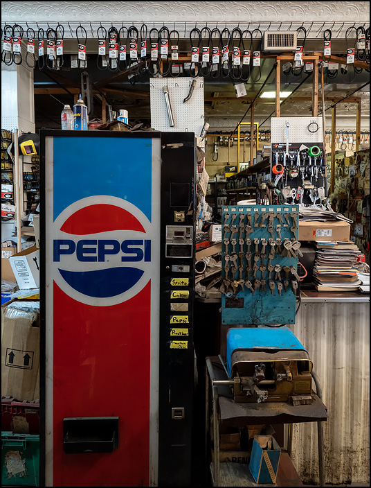 A Pepsi machine and an ancient key grinder with a display of keys stand in front of the sales counter at Kendallville Auto Parts on Main Street in the small town of Kendallville, Indiana.