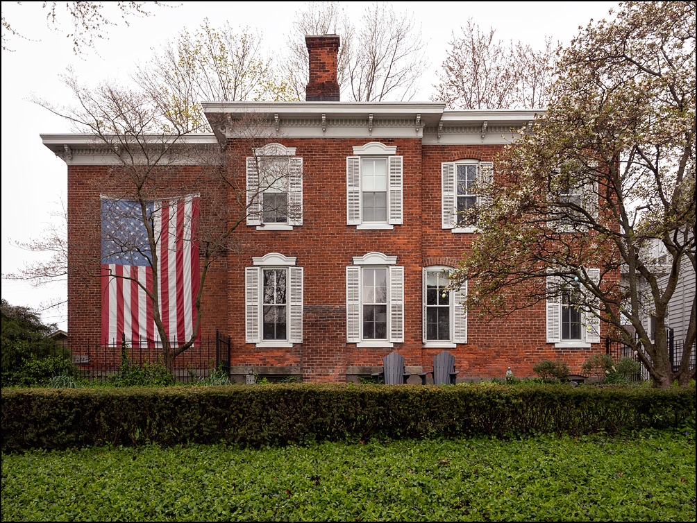 A very large American flag hanging on the front of a brick house on Kensington Boulevard in Fort Wayne, Indiana.
