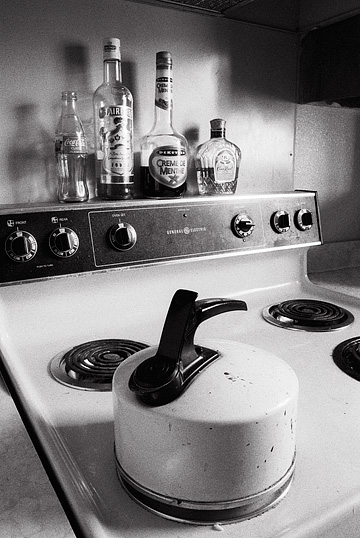 An old enameled tea kettle sits on the stove with half-empty liquor bottles behind it. Crown Royal, Smirnoff vodka, and Dekuyper creme de menthe.