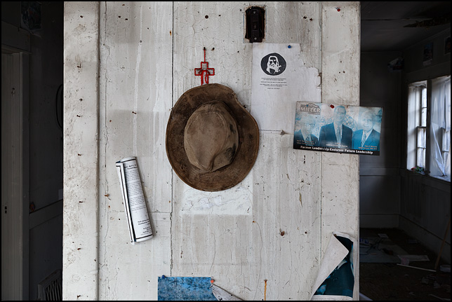 An old dirty khaki hat  and a cross hanging on the wall of an abandoned house. A paper with the Jesus Illusion and a faded political ad for Eric Miller, Republican for Governor, are nailed to the wall next to the hat.