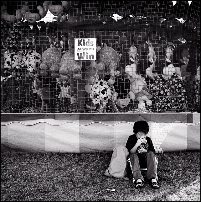 A little boy sits on the ground next to a carnival game tent eating a snack. The sign on the tent above the child says Kids Always Win.