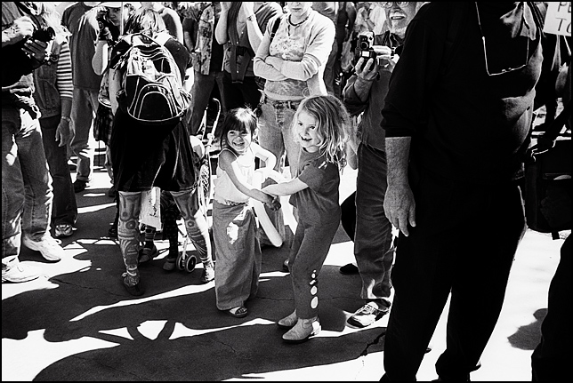 Two cute little girls dancing with a big balloon in the middle of a large crowd of people during an antiwar rally in Santa Fe, New Mexico.