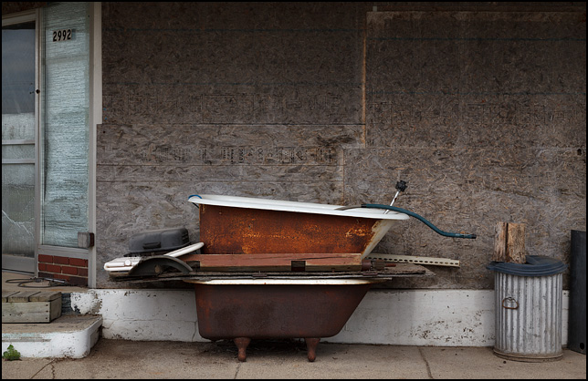 A stack of old rusty cast iron bathtubs in front of a vacant storefront on Clark Street in the small town of Kimmell, Indiana.