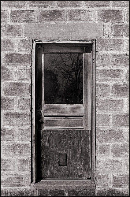 The weathered wood door and window on a small cinderblock building on Noe Street in the small town of Kimmell, Indiana.