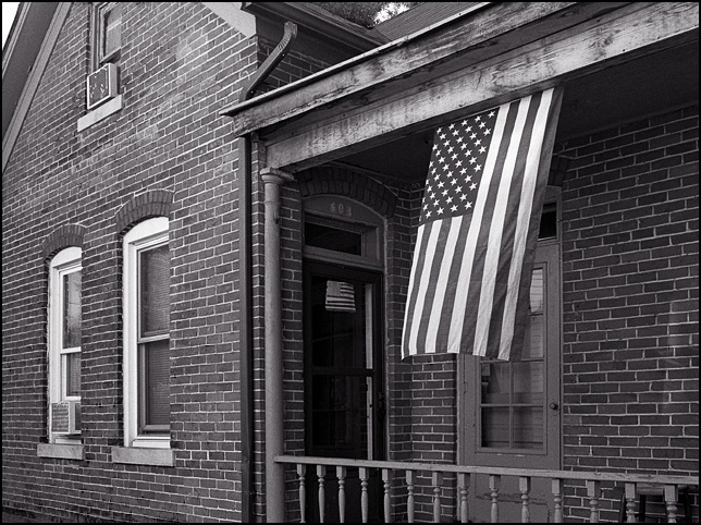 An American flag hanging from the porch of an old brick house on Kinnaird Avenue in Fort Wayne, Indiana. A paper American flag made by a child is taped on the front door.
