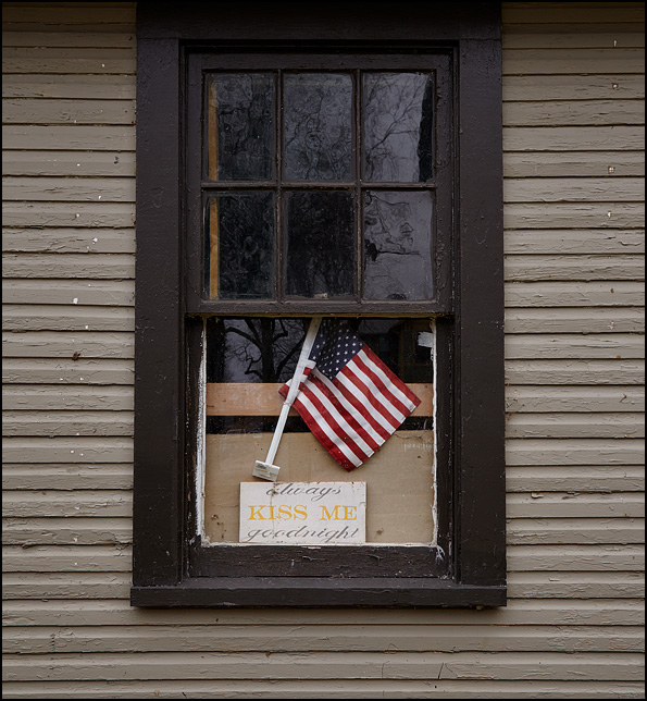 An American flag and a romantic sign hang in the window of an old garage in the West Central Neighborhood in Fort Wayne, Indiana. The sign says, Always Kiss Me Goodnight.