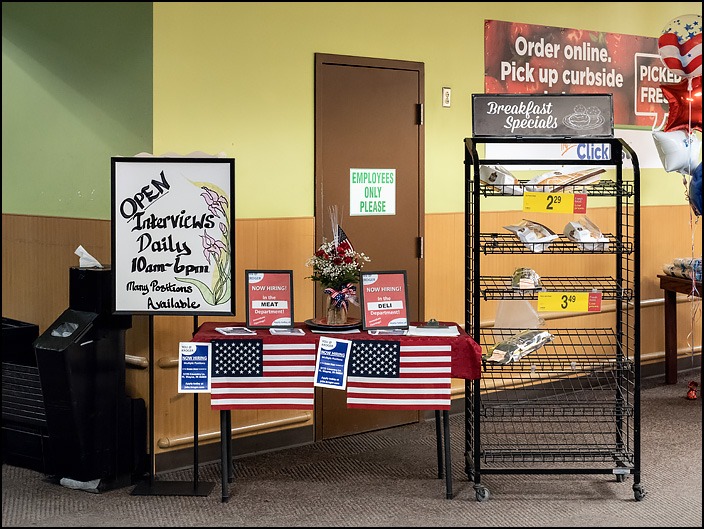 American flags decorate a hiring table with signs offering jobs at a Kroger store on the day after Memorial Day in Fort Wayne, Indiana.
