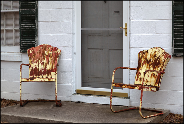 A pair of rusty yellow metal tulip chairs on the front step of a white cinderblock house on Kyle Road in Fort Wayne, Indiana.