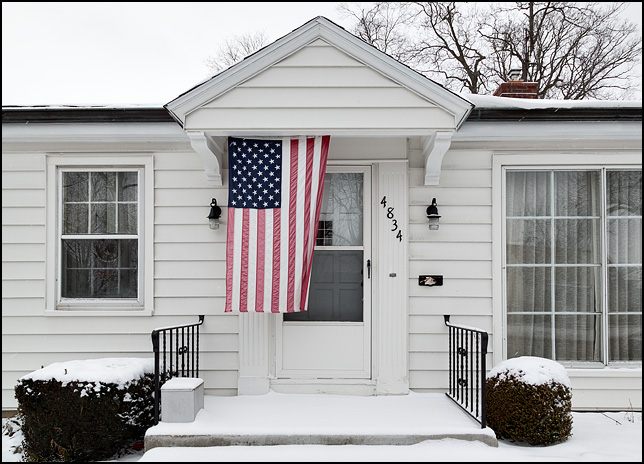 An American flag hangs in front of the door on a little white house on Lafayette Street in Fort Wayne, Indiana. The home and the yard were covered in snow.