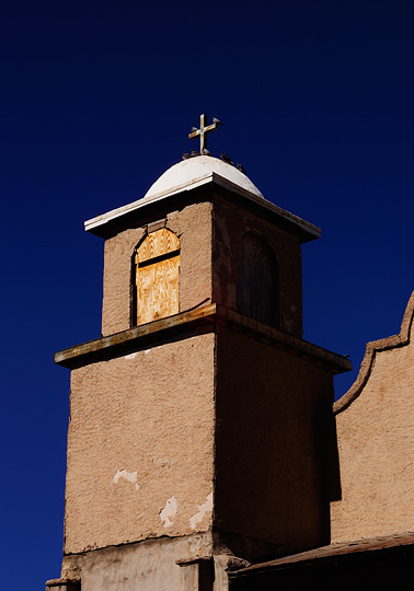 Birds perch on the cross and dome on the bell tower of the old church at Lamy, New Mexico.