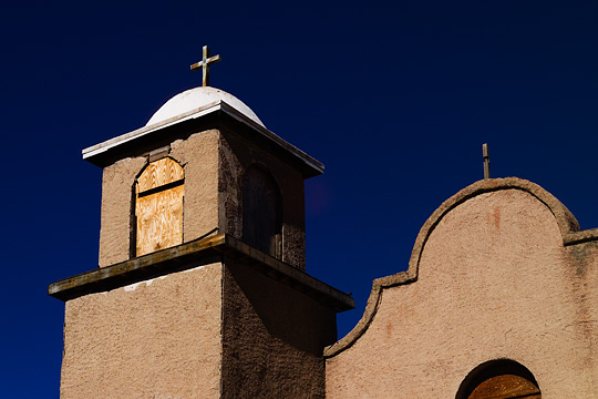 The bell tower on the old adobe church in Lamy, New Mexico. The tower is topped with a white dome and a large crucifix or cross.