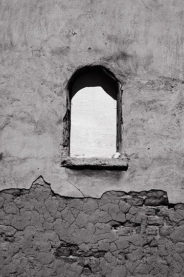 A boarded up window on the steeple tower of the old adobe church in Lamy, New Mexico. The plaster is cracked and falling away to reveal the adobe bricks that the church was built with.
