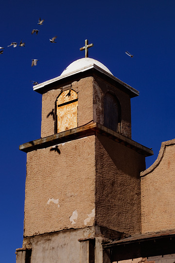 Birds fly around the steeple and bell tower of the abandoned adobe church in Lamy, New Mexico.