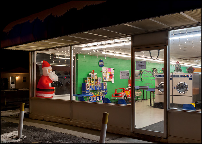 A life-size inflatable Santa Claus stands in the window of Georges Quik Wash, a laundromat in the Waynedale area of Fort Wayne, Indiana. Photographed at night, the empty laundromat looks deserted.