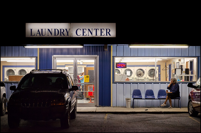 A woman sits in front of a laundromat talking on her cellphone and drinking coffee at night in the small town of Churubusco, Indiana.