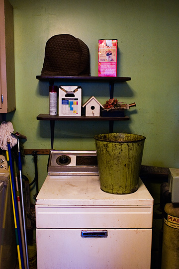 An old washer and dryer in my grandfather's laundry room. A trash can sits on top of the dryer, and a little birdhouse sits on a shelf above the appliances.