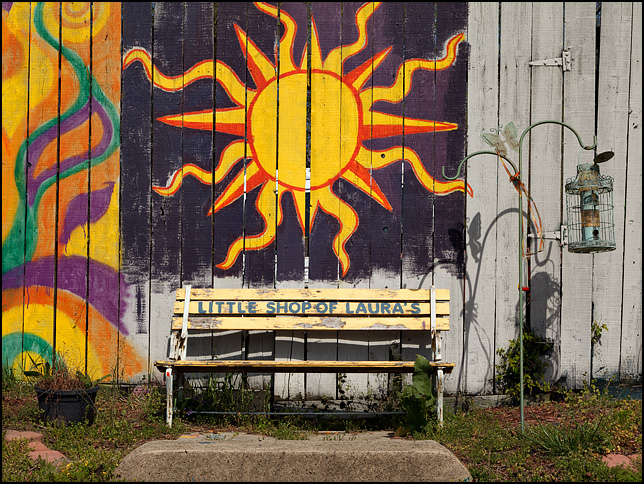 A yellow park bench sits on top of a hill in front of a wooden fence that is covered in murals.The painting above the bench is a sunburst. This is outside Little Shop of Lauras on Broadway in Fort Wayne, Indiana.