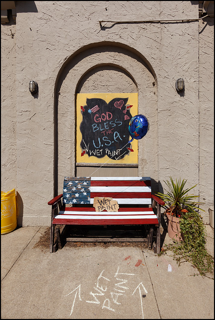 God Bless The USA. A sign written on a chalkboard above a bench painted like the American flag next to Little Shop of Lauras on Broadway in Fort Wayne, Indiana. There are handwritten signs on the bench that say, Wet Paint.