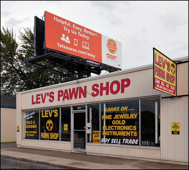 A large billboard for 1st Source Bank stands above Levs Pawn Shop on Lower Huntington Road in the Waynedale area of Fort Wayne, Indiana.