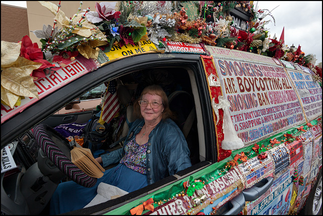 Smokers rights activist Lynda Farley sitting in the drivers seat of her minivan, the Liberty Van, which is completely covered in political and religious signs.